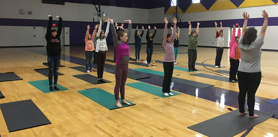Multiple students standing in Gym with the Yoga mats with hands in air.