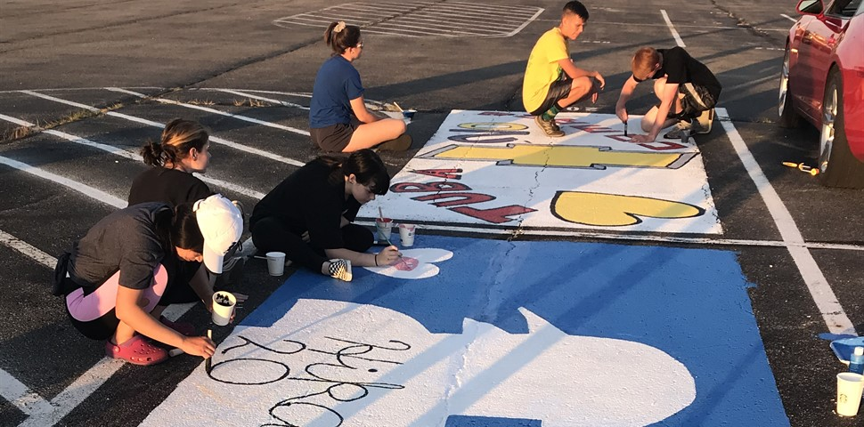 STUDENT AT HS SHOWN PAINTING THEIR HS PARKING SPOT